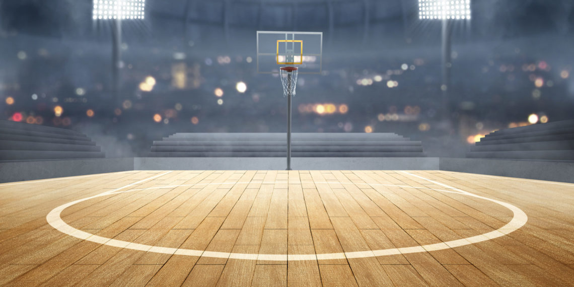 Basketball court with wooden floor, lights reflectors, and tribune over blurred lights background