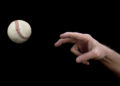 A man's arm throwing a baseball on a black background.