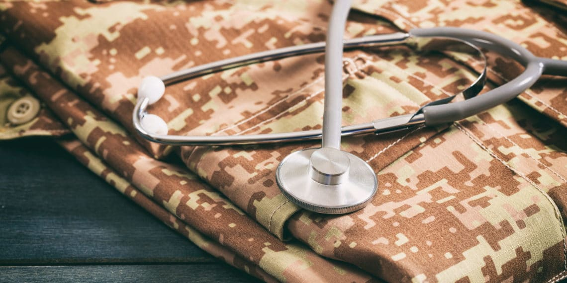 Military medical concept with stethoscope and American military digital pattern uniform, folden on wooden background