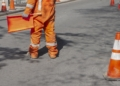 road worker directing traffic with orange flag and reflective suit