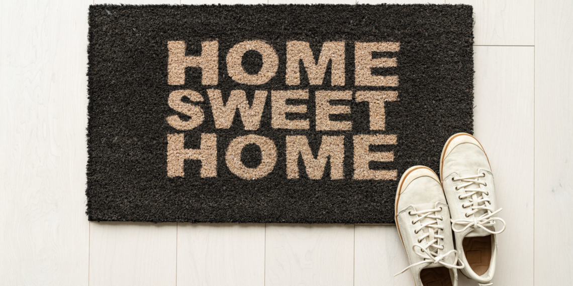 Home sweet home door mat at house entrance with women's sneakers of woman that has just arrived moved in. New condo.