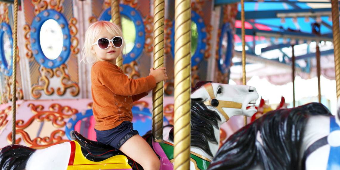 A cute llittle toddler girl in big fashionable sunglasses is riding on a classic carousal horse at a small town carnival.