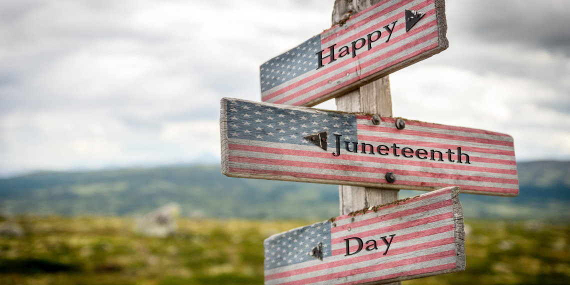 Happy juneteenth day text on wooden american flag signpost outdoors in nature.