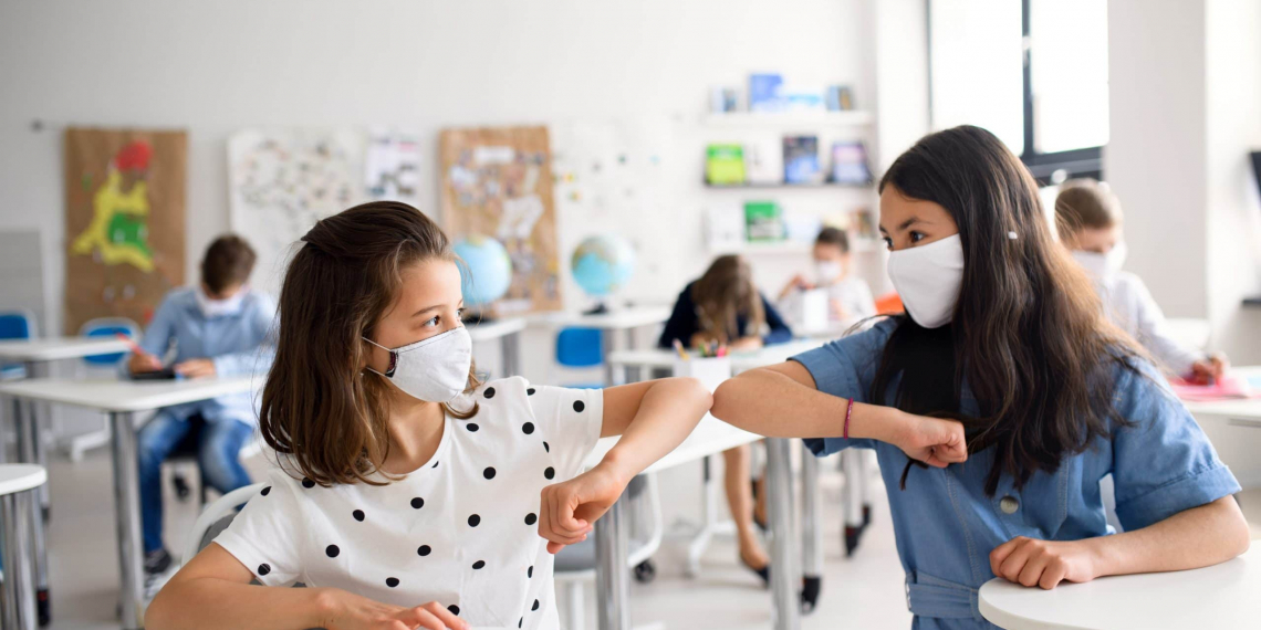 Small children with face mask back at school after covid-19 quarantine and lockdown, greeting.