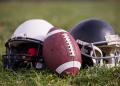 American football helmets and ball lying on field