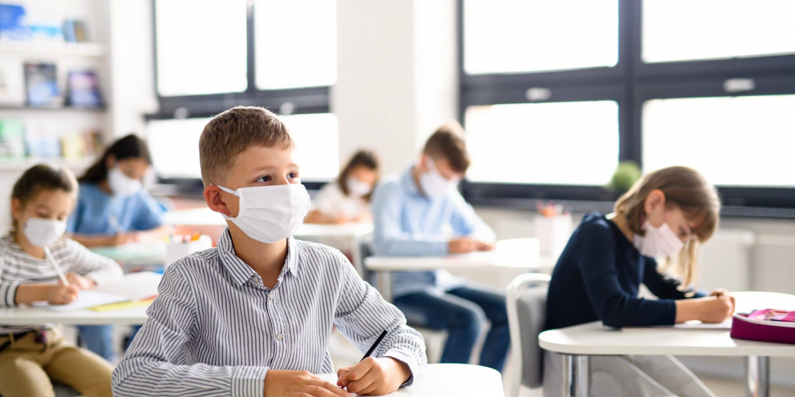 Small children with face mask back at school after covid-19 quarantine and lockdown.