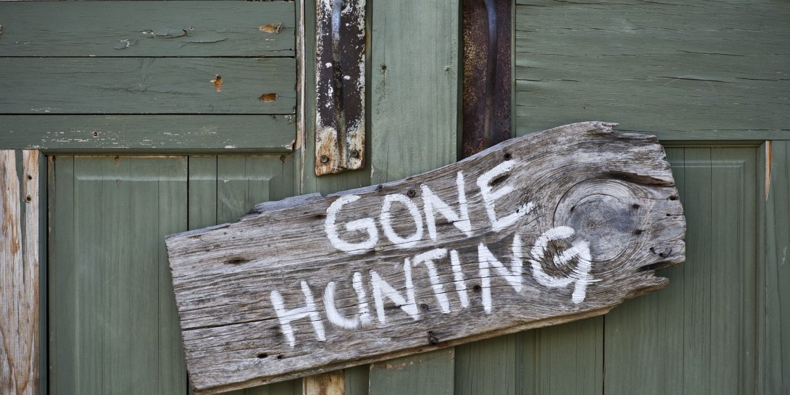 Old gone hunting sign on green doors.