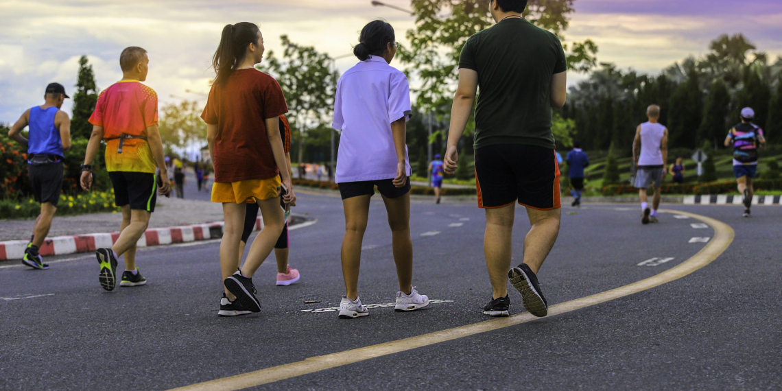 Group of healthy people walking jogging with sunset in city park.
