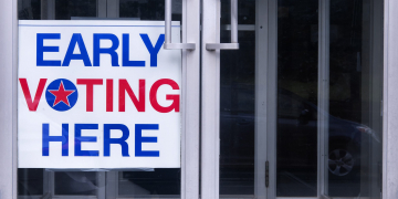 An early voting sign on a door welcoming people to vote for an democratic election in the united states of america.