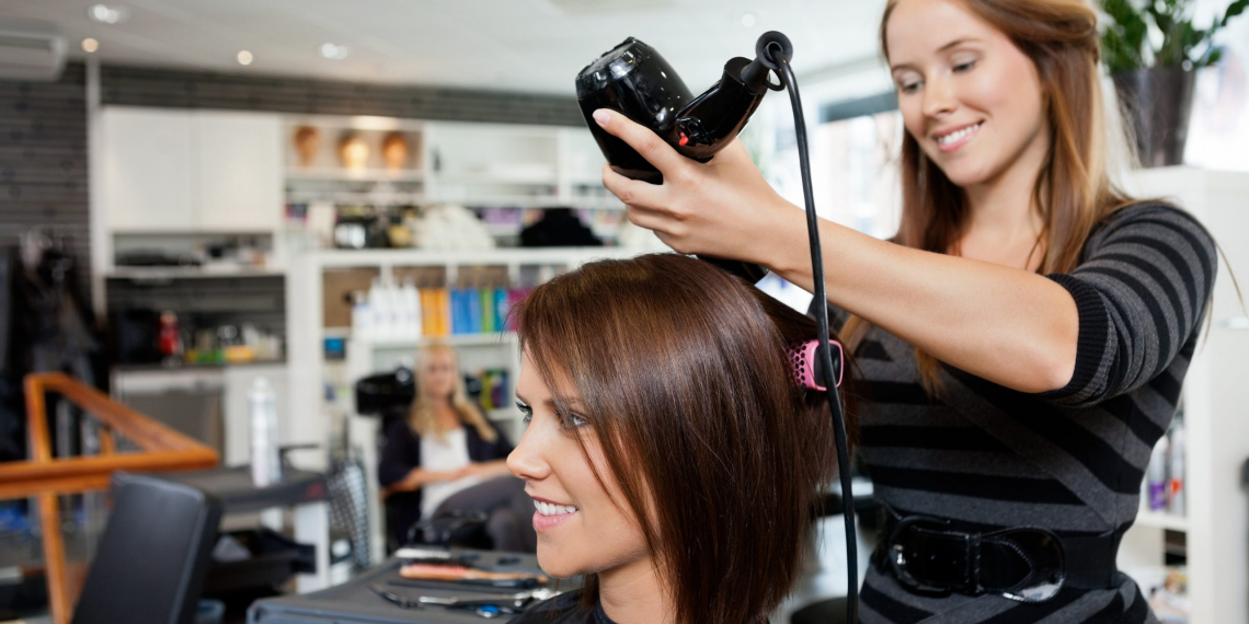 Beautician blow drying woman's hair after giving a new haircut at parlor