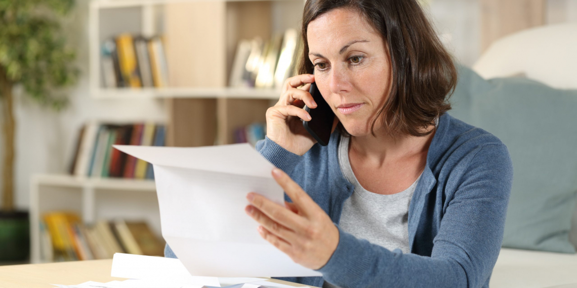 Serious adult woman checking letter calling on smart phone sitting in the livingroom at home