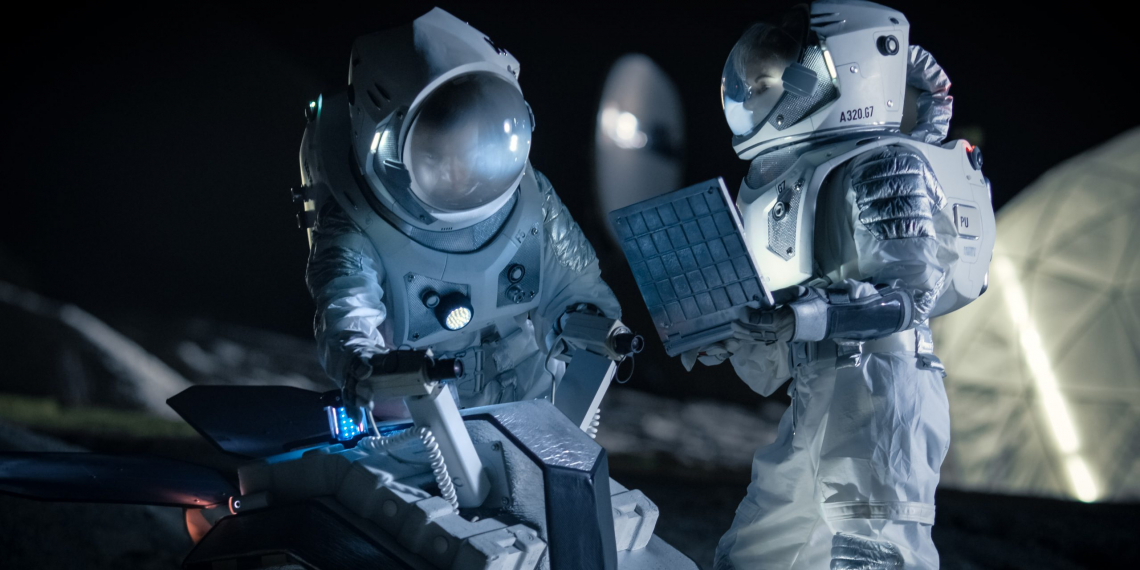 Two Astronauts in Space Suits on an Alien Planet Prepare Space Rover for Planet's Surface Exploration Expedition, Use Laptop. Space Travel and Solar System Colonization Concept.