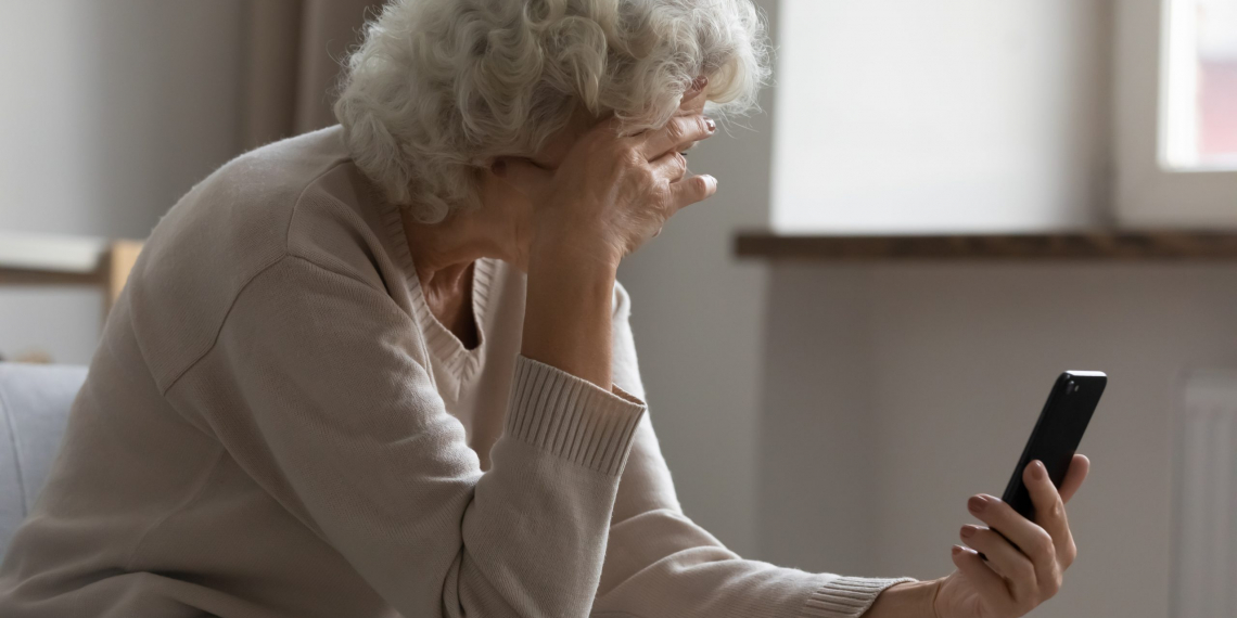 Sad elderly woman sit on sofa hold smartphone feels disappointed by received sms bad news, awful message, difficulties with modern device usage, unpleasant notification, stressed older person concept