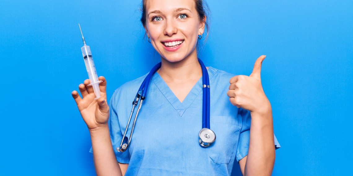 Young blonde woman wearing doctor uniform holding syringe smiling happy and positive, thumb up doing excellent and approval sign