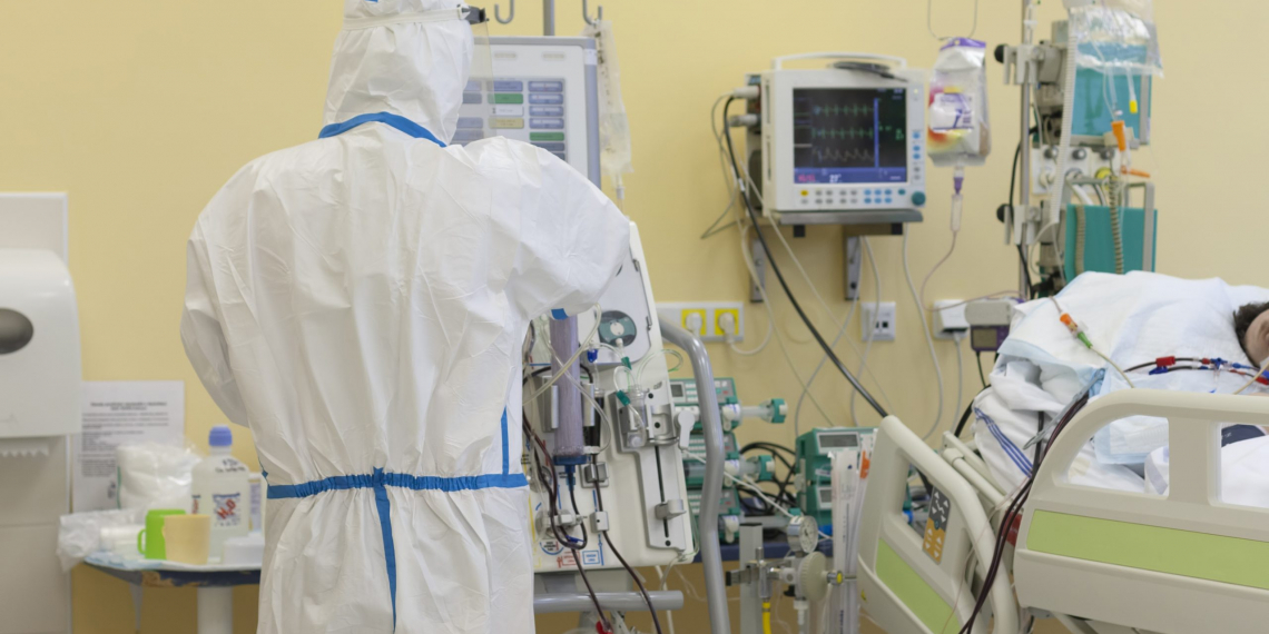 Male nurse with protective coverall clothing in intensive care unit in hospital.  Dialysis machine, to which patient is connected.  The patient fell ill with a new type of coronavirus covid-19.