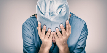 Crying doctor during COVID-19 needing help in hospital. Healthcare workers in despair over emergency need of PPE and distress. Coronavirus crisis death, dispair, mental health anxiety.