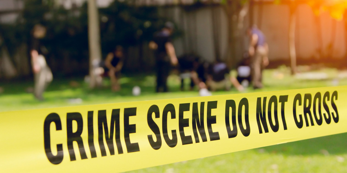 crime scene tape and blurred law enforcement team background